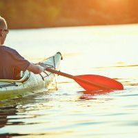 Kayaking couple ride along the river at sunset